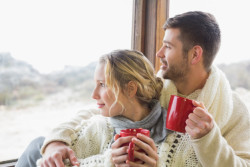 couple-in-winter-wear-with-cups-looking-out-through-window_13339-112588